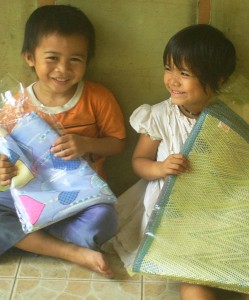 Two orphans receiving food, blankets, and a sleeping mat.